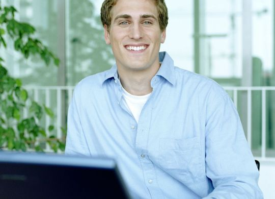 Young man using laptop, smiling, portrait